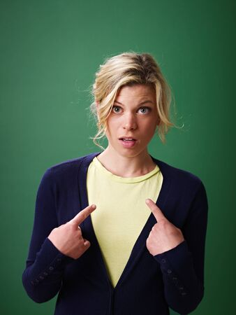 young woman pointing at herself against green background and looking at camera photo