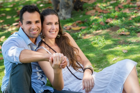 look latino: Happy beautiful young man and woman in love, lying on grass in park and relaxing