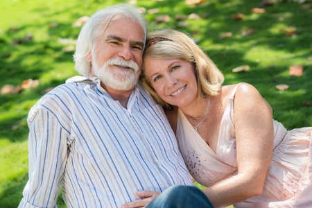 Old people and romance, elderly husband and wife in love, lying on grass in park photo