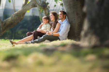 Happy family with man, woman and child leaning on tree in city park.