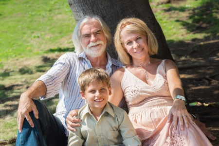 Happy grandfather and grandmother with grandson sitting on grass under tree in park photo