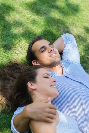 Happy beautiful young man and woman in love, lying on grass in park and relaxing photo