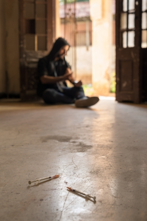 intoxication: Heroin junkie shooting up drugs with syringe. Low angle view, copy space