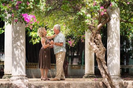 pareja bailando: Los jubilados activos que tiene el hombre divertido, feliz de edad y una mujer bailando la danza de Am�rica Latina en el patio