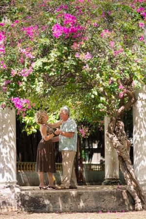 bailarines de salsa: Los jubilados activos que tiene el hombre divertido, feliz de edad y una mujer bailando la danza de América Latina en el patio