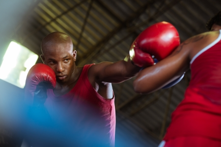 boxing match: Sport and people, two men exercising and fighting in boxing gym Stock Photo