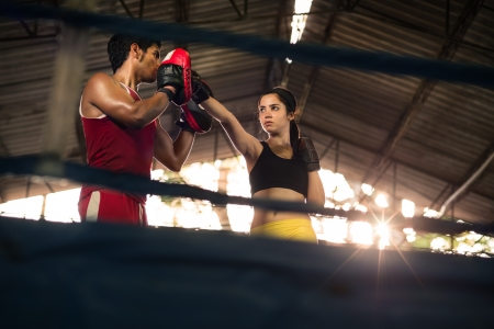 boxing training: Young woman exercising with trainer at boxe and self defense lesson. Copy space Stock Photo