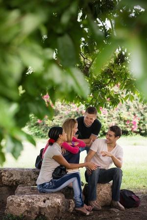 pareja de adolescentes: La gente y la educaci�n, estudiantes universitarios reunidos y hacer los deberes juntos en el parque