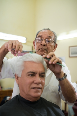 Active retired old people, man getting an haircut by senior barber in old fashion barber's shop. Copy space photo