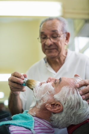 Elderly barber with shave brush applying cream to client in old style shop photo