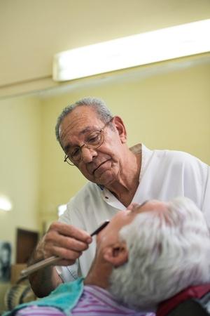peluquero: Hombre mayor en el trabajo como barbero afeita cliente con navaja en la tienda de moda de edad
