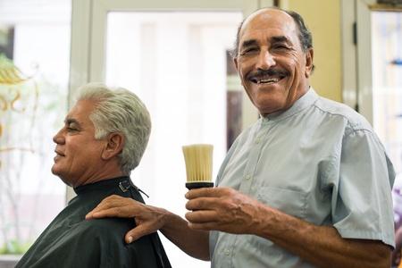 barber shop: Oude kapper houdt borstel voor Talco en glimlachen naar de camera in ouderwetse kapperszaak Stockfoto