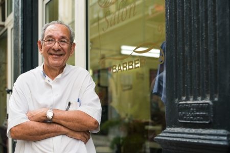 barbero: barbero alto hispano en una peluquería de moda antigua, posando y mirando a la cámara con los brazos cruzados cerca de escaparate Foto de archivo