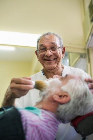 Elderly barber with shave brush applying cream to client in old style shop, smiling at camera photo