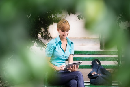 Portrait of happy young female college student typing on digital tablet computer and sitting on bench in city park photo