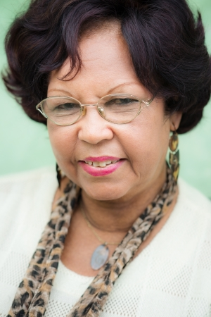 Portrait of happy old african american woman with glasses and wig smiling at camera photo