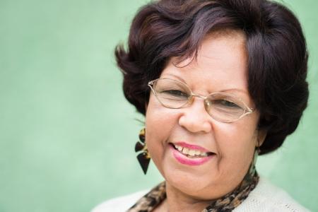 mujeres ancianas: Retrato de feliz vieja mujer afro-americana con gafas y peluca sonriendo a la cámara