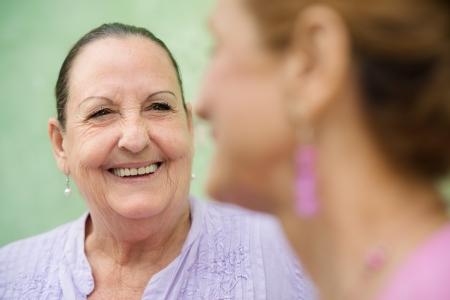 dos personas conversando: Retirados los ancianos y las actividades de ocio, las mujeres mayores que hablan en parque de la ciudad Foto de archivo