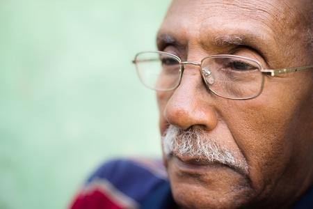 mirada triste: Personas mayores y los sentimientos de tristeza, retrato viejo negro con gafas y bigote. Copiar el espacio