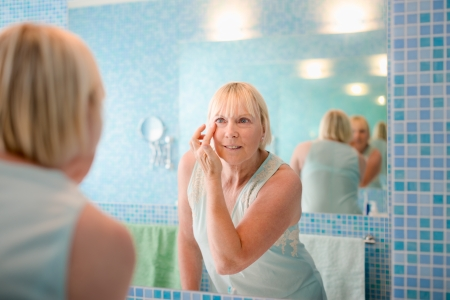 body grooming: Female beauty, senior caucasian woman applying lotion on face in bathroom at home