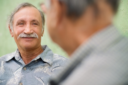 conversations: Retired elderly people and friendship, two old men meeting and talking in city park