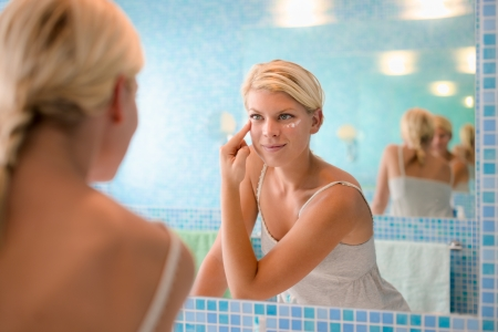 lotions: Female beauty, beautiful young caucasian woman applying cream on face in bathroom at home Stock Photo