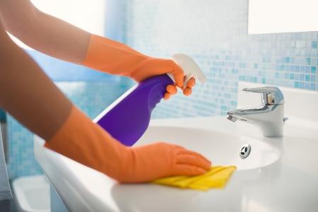 detersivi: donna facendo lavoretti in bagno a casa, pulire lavandino e rubinetto con detergente a spruzzo. Ritagliate la vista Archivio Fotografico