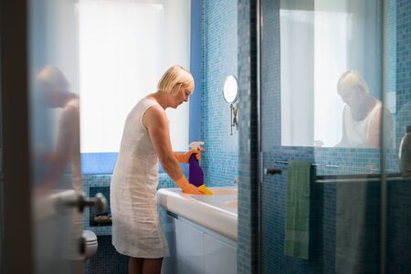 housewife gloves: Active retirement and old people, elderly woman doing chores in bathroom at home, cleaning wash basin and tap with spray detergent