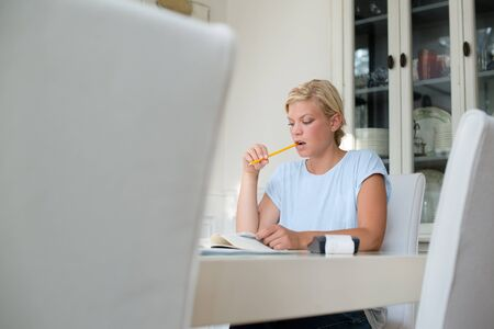 taxes budgeting: Home finance, personal savings, and financial planning, young caucasian woman checking bills and doing budget with calculator and papers