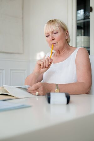 taxes budgeting: Home finance, personal savings, and financial planning, old caucasian woman checking bills and doing budget with calculator and papers