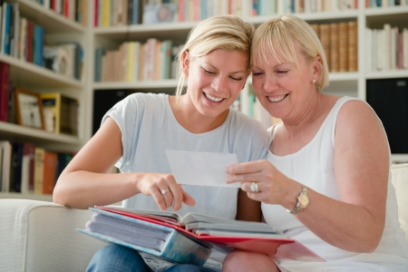 happy mom and daughter looking at pictures in photo album Stock Photo - 15553973