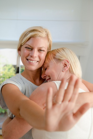 young woman showing engagement ring to her mother and hugging Stock Photo - 15553974