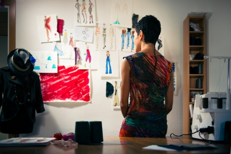 atelier: Young people and small business, hispanic woman at work as fashion designer and tailor, looking at sketches of new collection in atelier
