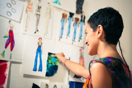 fashion: Young people and small business, hispanic woman at work as fashion designer and tailor, looking at sketches of new collection in atelier
