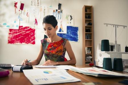 contabilidad: El dinero y la planificaci�n financiera, el joven hispano por cuenta propia mujer comprobando facturas y hacer presupuesto con la calculadora, el ordenador y los documentos de dise�o de moda en estudio