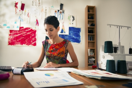 Money and financial planning, young hispanic self-employed woman checking bills and doing budget with calculator, computer and papers in fashion design studio photo