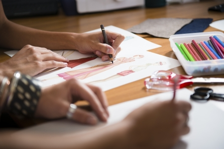 creative industries: two young women working as fashion designers and drawing sketches for clothes in atelier. Cropped view Stock Photo