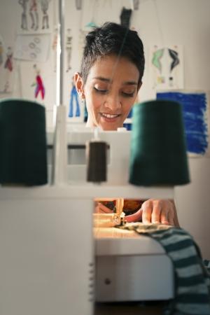maquina de coser: Las peque�as empresas y las trabajadoras aut�nomas, mujer joven hispano trabajando como dise�ador de moda con la m�quina de coser en el taller Foto de archivo