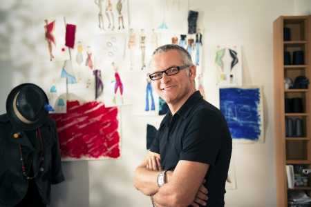 Confident entrepreneur, portrait of happy mature man working as fashion designer and dressmaker in atelier photo