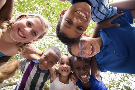niños jugando en el parque: Grupo de felices los niños de ambos sexos que se divierten y abrazos alrededor de la cámara. Ángulo de visión baja