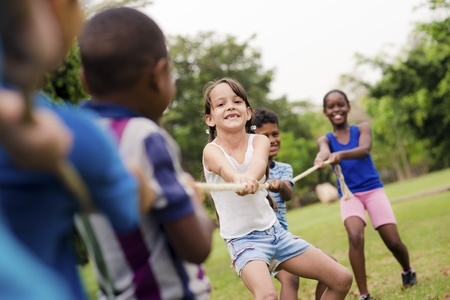 Children and recreation, group of happy multiethnic school kids playing tug-of-war with rope in city park. Summer camp fun Stock Photo