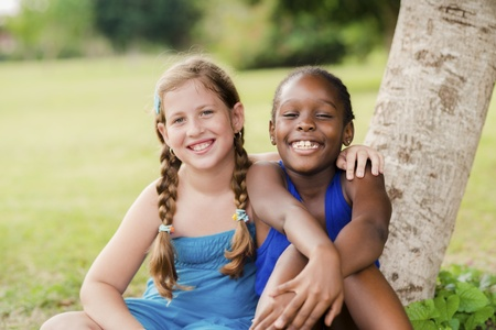 best schools: Children and friendship, portrait of two young girls hugging, smiling and looking at camera while sitting near tree in park
