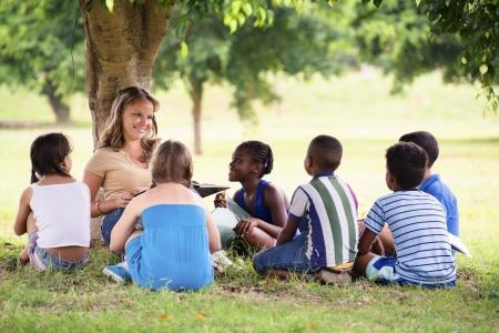 Kinderen en onderwijs, jonge vrouw op het werk als opvoeder leesboek voor jongens en meisjes in park Stockfoto