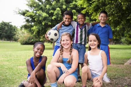niños latinos: Los muchachos jóvenes y el deporte, retrato de tres niños pequeños con el fútbol mirando a la cámara. Verano divertido campamento