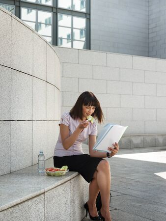 mid adult business woman doing lunch break with fresh salad and reading paperwork out of office building photo