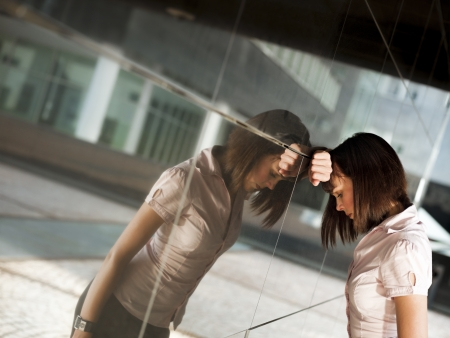 banging: sad caucasian business woman banging her head against a wall out of office building. Reflection on wall