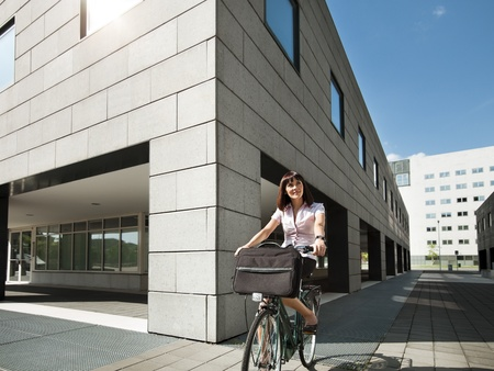 biking: mid adult caucasian business woman commuting to office by bike and smiling