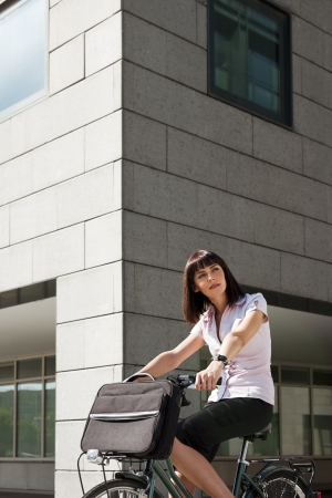 mid adult caucasian business woman commuting to office by bike and looking away photo