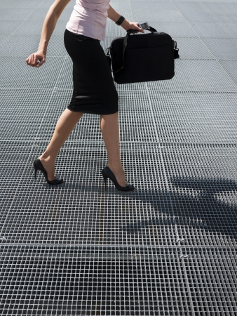 cropped view of mid adult business woman walking on high heels, trying to balance on grating Stock Photo - 15893985