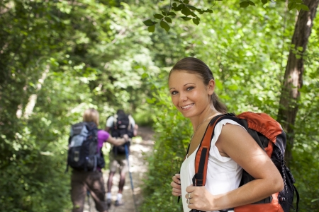 waist up: group of man and women during hiking excursion in woods, with woman looking at camera and smiling. Waist up